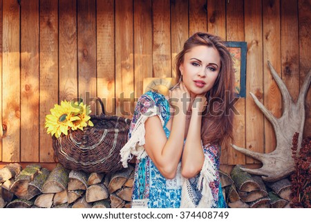 portrait of a beautiful sexy woman standing and posing outdoors on the background of wood  in the garden - stock photo