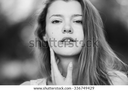 Portrait of a beautiful sexy young girl with perfect skin and make-up closeup. Emotional photo. Black and white