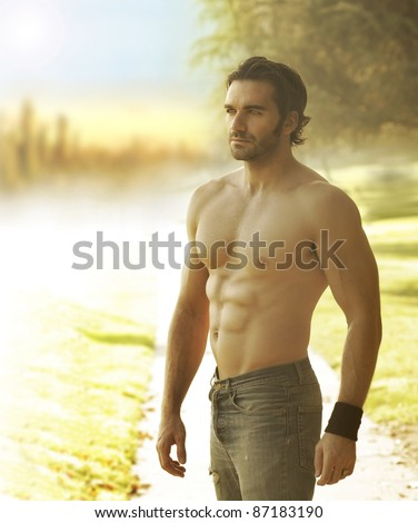 Portrait of a beautiful shirtless man in jeans against the light in natural outdoor setting - stock photo