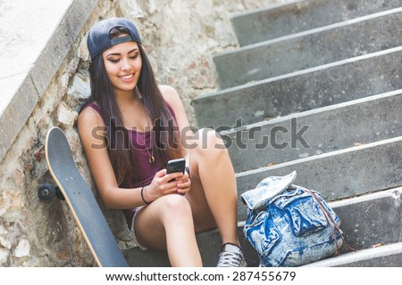 Portrait of a beautiful skater girl looking at smart phone at park. She is half caucasian and half filipina, she wears short jeans, a purple tank top and a black cap. - stock photo
