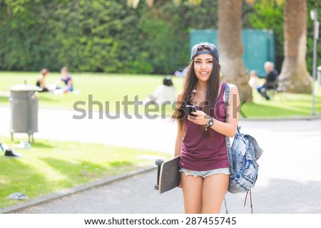 Portrait of a beautiful skater girl looking at smart phone at park. She is half caucasian and half filipina, she wears short jeans, a purple tank top and a black cap.
