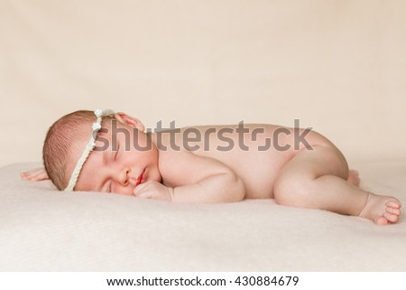 Portrait of a beautiful sleeping baby in the wreath , newborn girl