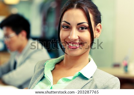 Portrait of a beautiful smiling businesswoman in office - stock photo