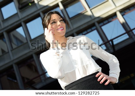 Portrait of a beautiful smiling businesswoman on the phone in a office building - stock photo
