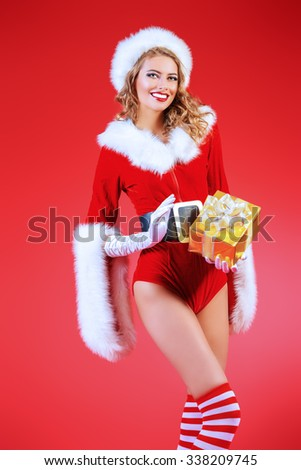 Portrait of a beautiful smiling Christmas girl with a gift box. Red background. - stock photo