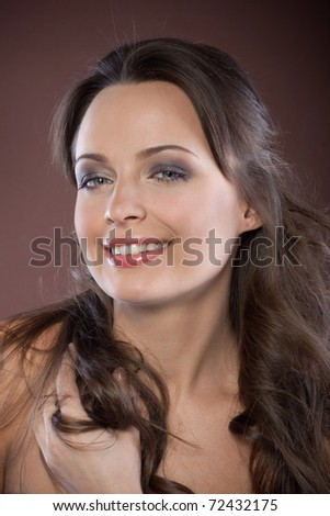 Portrait of a beautiful smiling dark-haired girl on a chocolate background. - stock photo