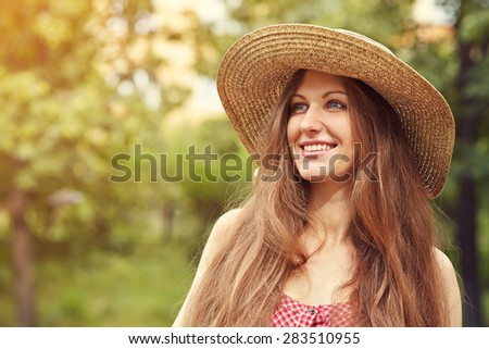 portrait of a beautiful smiling dreaming woman in a hat in a summer park - stock photo