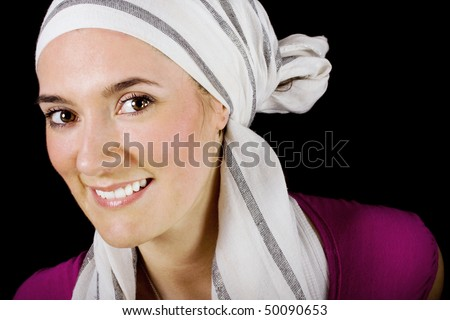 Portrait of a beautiful smiling fashionable stylish woman with head dress on black background