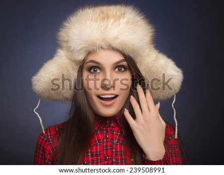 portrait of a beautiful smiling girl in a fur cap on background