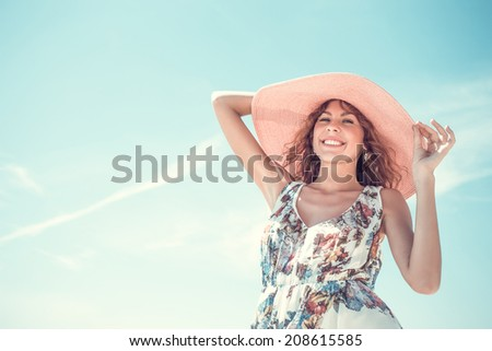 portrait of a beautiful smiling girl in hat and dress on a background of sky