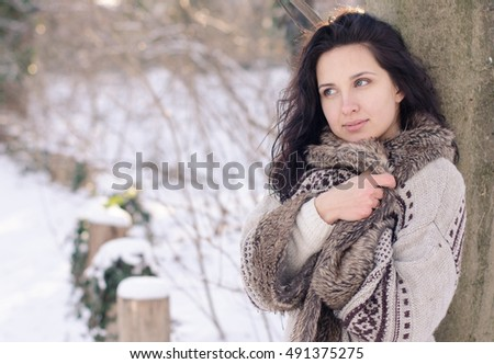 Portrait of a beautiful smiling girl near the tree in winter