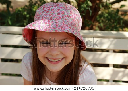 Portrait of a beautiful smiling little girl in panama on the bench in summer garden on a sunny day - stock photo