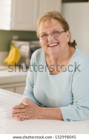 Portrait of a Beautiful Smiling Senior Adult Woman in Kitchen. - stock photo