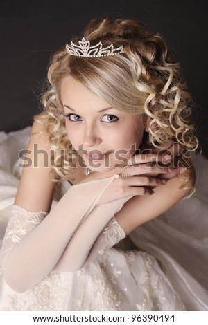Portrait of a beautiful smiling woman dressed as a bride over gray background.