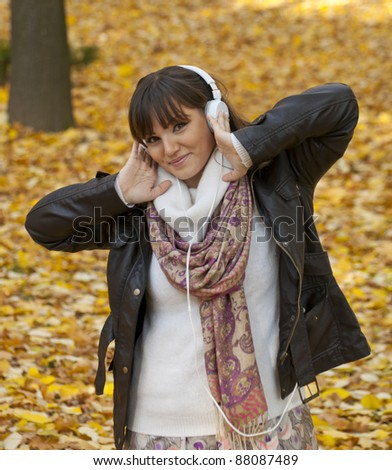 Portrait of a beautiful smiling woman listening to music - stock photo