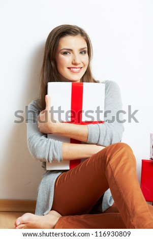 Portrait of a beautiful smiling woman seat on the floor with many christmas gift against white wall background.