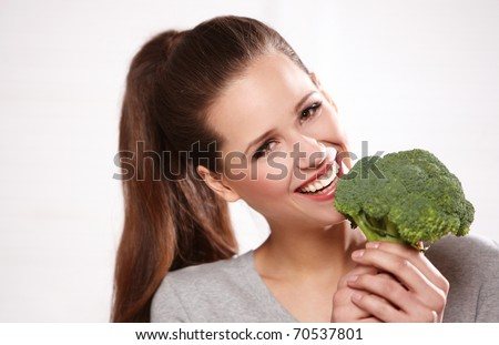 Portrait of a beautiful smiling woman with broccoli, isolated on white - stock photo
