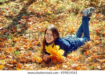 portrait of a beautiful smiling woman with yellow maple leaves in autumn