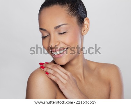 Portrait of a beautiful smiling young African woman, with closed eyes and fingers on her shoulder Beauty concept - stock photo