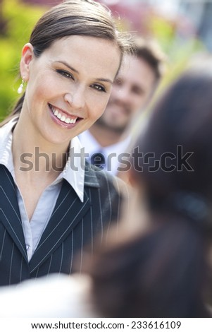 Portrait of a beautiful smiling young business woman or businesswoman with colleagues in team meeting outside - stock photo