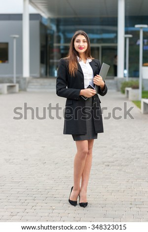 Portrait of a beautiful smiling young business woman with modern building as background. - stock photo