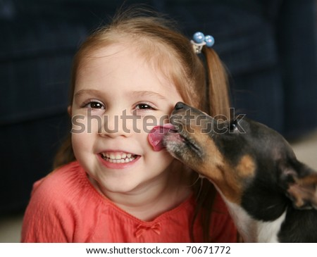 Portrait of a beautiful smiling young girl being licked on the cheek by a cute terrier puppy dog - stock photo