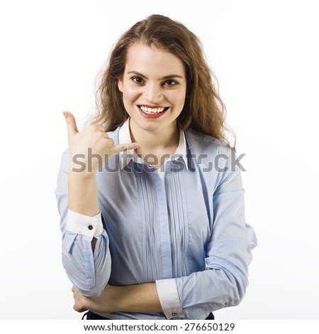 Portrait of a beautiful smiling young woman dressed in a blue shirt on a white background in  gesture calling - stock photo