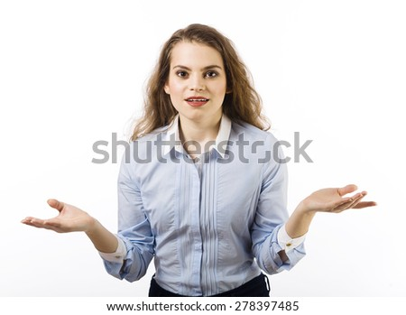 Portrait of a beautiful smiling young woman dressed in a blue shirt on a white background in a gesture indicating - stock photo