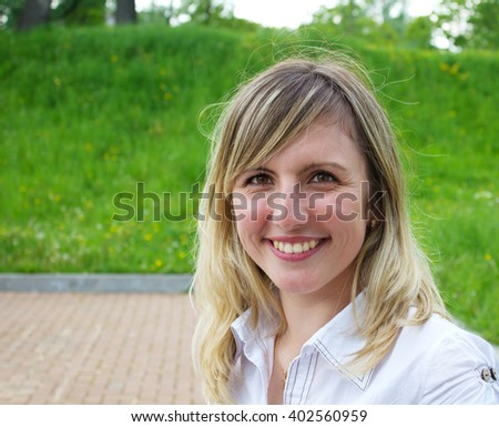 portrait of a beautiful smiling young woman outside on spring day