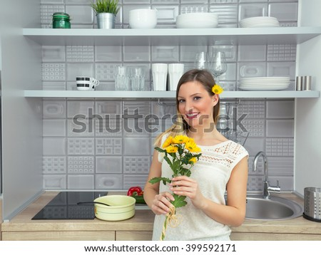 Portrait of a beautiful smiling young woman standing in a modern kitchen with a bouquet of yellow flowers, and a single flower in her hair
