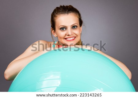 Portrait of a beautiful sports woman exercising with pilates ball over gray background - stock photo
