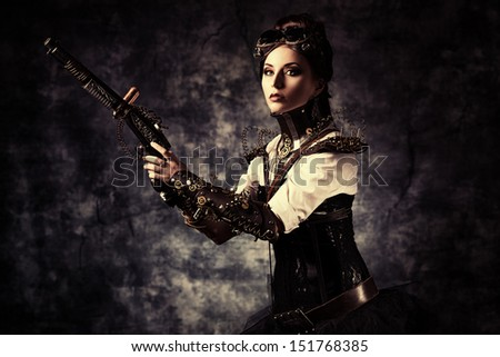 Portrait of a beautiful steampunk woman holding a gun over grunge background.