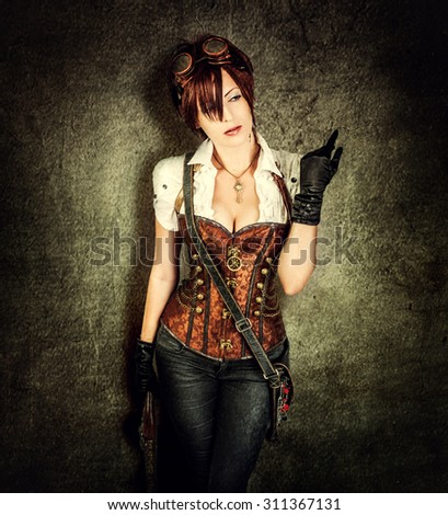 Portrait of a beautiful steampunk woman wearing vintage corset and retro goggles on old grange background