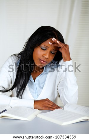 Portrait of a beautiful student with headache browsing a book at home indoor - stock photo