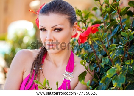 portrait of a beautiful Summer Woman on vacation near flowers - stock photo