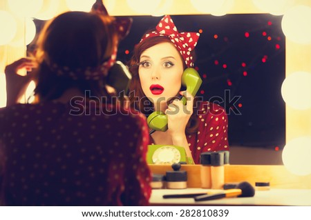 Portrait of a beautiful surprised woman with a dial phone and applying cosmetics near a mirror. Photo in retro color style. - stock photo