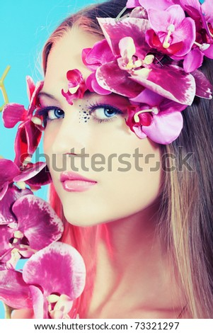 Portrait of a beautiful tanned woman in bikini posing with flowers.