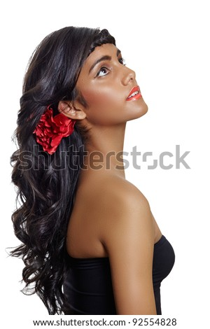 portrait of a beautiful tanned young woman with long brown curly hair and red flower, wearing red lipstick and black dress, sitting in profile on white background - stock photo