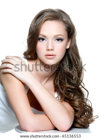 Portrait of a beautiful teen girl with  long curly hairs and clean skin of the face - isolated on white