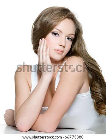Portrait of a beautiful teen girl with  long curly hairs and clean skin of the face - isolated on white - stock photo