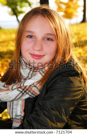 Portrait of a beautiful teenage girl in a fall park with fallen leaves