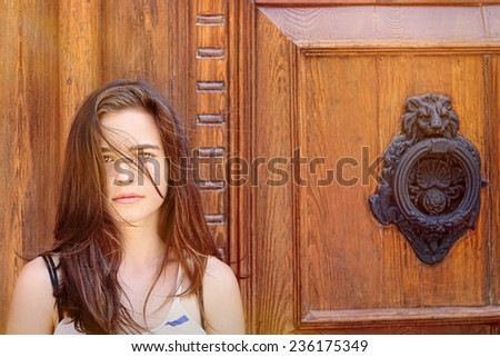 portrait of a beautiful teenage girl in front of an ancient wood door - stock photo