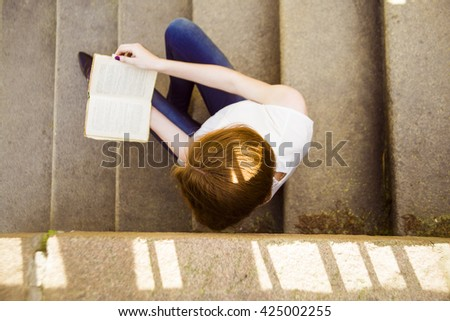 Portrait of a beautiful teenage student girl sitting on stairs in park with copy book and studying. Sunny summer day. casual lifestyle. Woman with note pad. top view. - stock photo