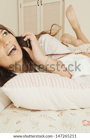 Portrait of a beautiful teenager relaxing and laying down on her bed in her bedroom at home, using a mobile phone to have a conversation with friends, smiling and flirting.