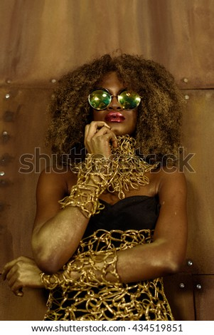 Portrait of a beautiful thoughtful young African woman wearing gold jewelry and sunglasses holding hand near face, bronze background - stock photo