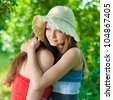 Portrait of a beautiful two young elegant women gently and friendly hugging in compassion and support in the park or garden on a bright sunny day of summer on the green trees background - stock photo