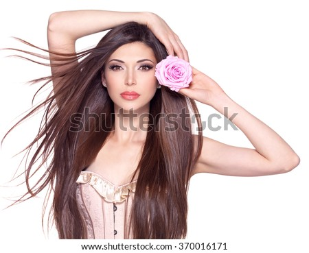 Portrait of a beautiful white pretty woman with long straight hair and pink rose at face. - stock photo