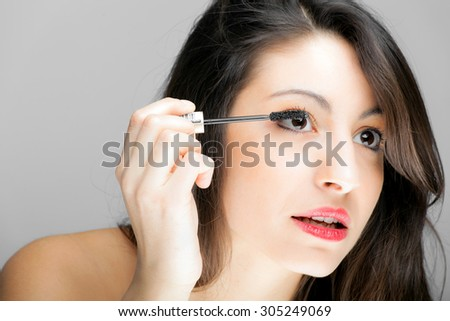 Portrait of a beautiful woman applying makeup  - stock photo