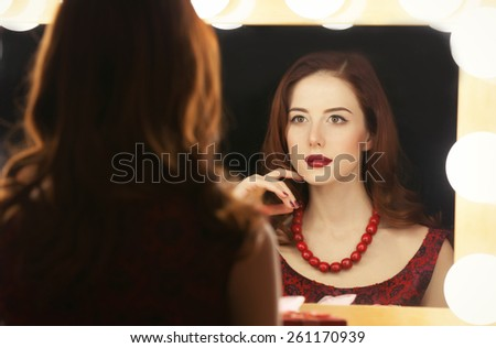 Portrait of a beautiful woman as applying makeup near a mirror.  - stock photo