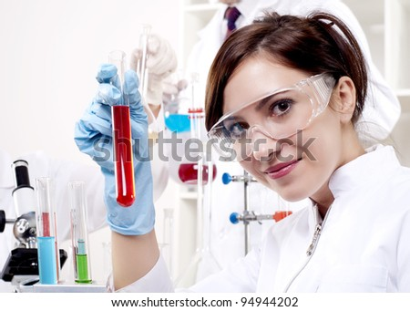 portrait of a beautiful woman chemist, looks at a test tube with red fluid - stock photo